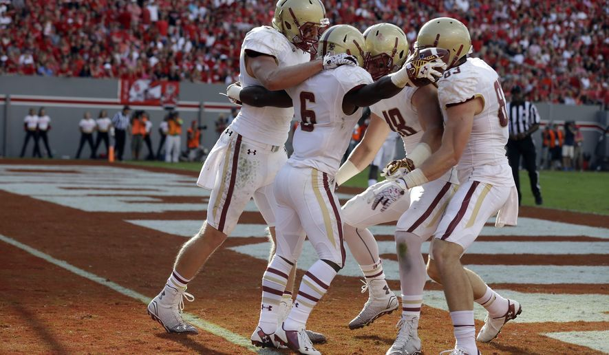 Boston College's Sherman Alston (6) is congratulated by Dan Crimmins (18), Charlie Callinan (83) and Josh Bordner, left, following Alston's touchdown against North Carolina State during the first half of an NCAA college football game in Raleigh, N.C., Saturday, Oct. 11, 2014. (AP Photo/Gerry Broome)