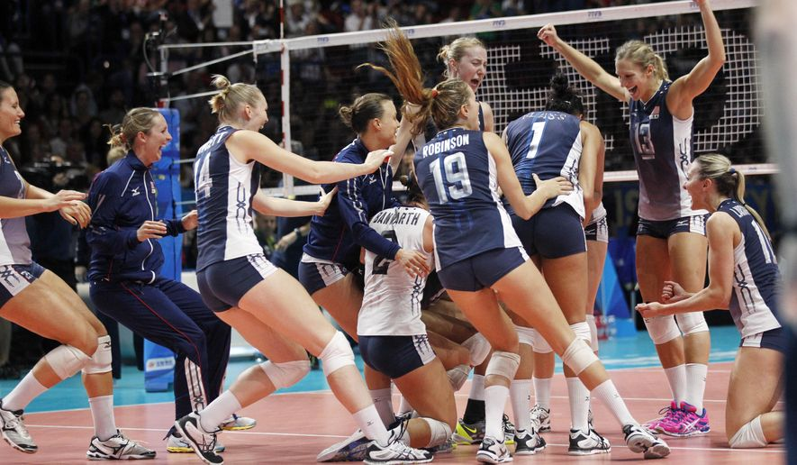 United States' players celebrate after defeating Brazil during a semifinal volleyball match, at the women's Volleyball World Championships in Milan, Italy, Saturday, Oct. 11, 2014. (AP Photo/Felice Calabro')