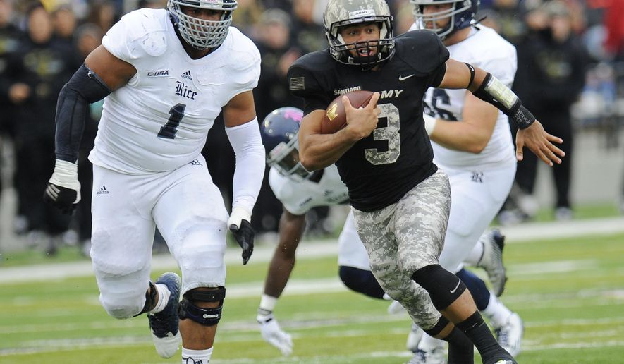 Rice defensive tackle Christian Covington (1) chases Army quarterback Angel Santiago (3) during the first half of an NCAA college football game on Saturday, Oct. 11, 2014, in West Point, N.Y. (AP Photo/Hans Pennink)