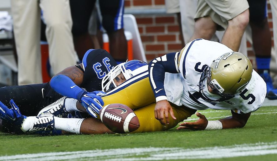 Georgia Tech quarterback Justin Thomas (5) fumbles the ball as he is tackled by Duke safety Deondre Singleton (33) in the second half of an NCAA college football game Saturday, Oct. 11, 2014, in Atlanta.  Duke won 31-25. (AP Photo/John Bazemore)