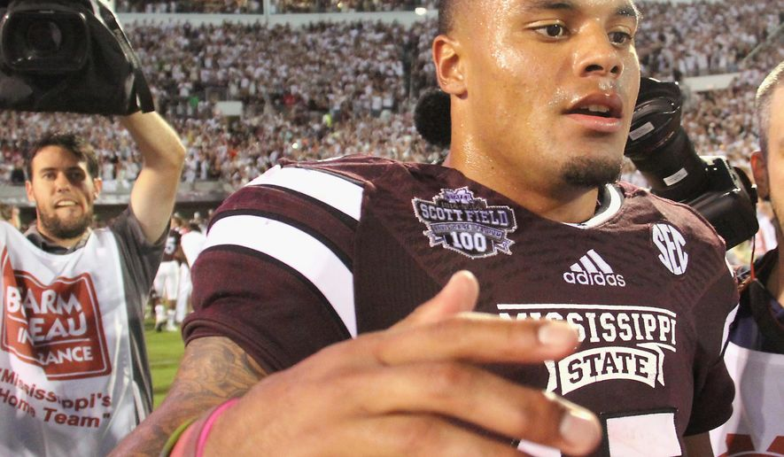 Mississippi State quarterback Dak Prescott (15) walks through off the field following their 38-23 win over No. 2 Auburn in an NCAA college football game in Starkville, Miss., Saturday, Oct. 11, 2014. (AP Photo/Jim Lytle)