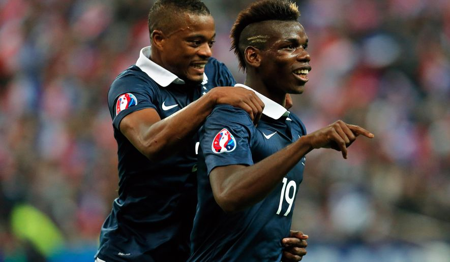 France's Paul Pogba, right, celebrates after scoring with his teammate Patrice Evra, during their international friendly soccer match against Portugal, at the Stade de France, in Saint Denis, north of Paris, France, Saturday, Oct. 11, 2014. (AP Photo/Thibault Camus)