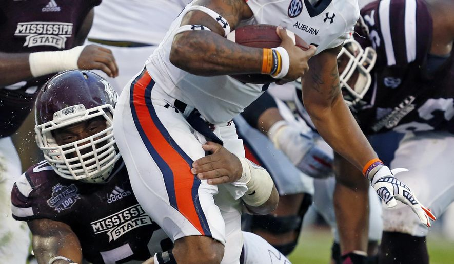Mississippi State linebacker Benardrick McKinney (50) tries to tackle Auburn quarterback Nick Marshall (14) in the second half of an NCAA college football game in Starkville, Miss., Saturday, Oct. 11, 2014. Mississippi State won 38-23. (AP Photo/Rogelio V. Solis)