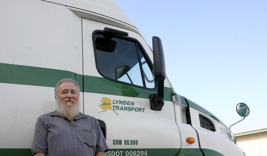Lynden Transportation Driver John Schank, left, stands near a truck at Lynden Transportation's Fairbanks Service Center in Fairbanks, Alaska on Thursday, Oct. 2, 2014. Schank was recognized  by Governor Sean Parnell for 37 years of accident-free driving on the Dalton Highway. (AP Photo/Fairbanks Daily News-Miner, Erin Corneliussen)