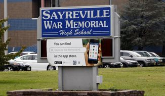 This Oct. 7, 2014, file photo, shows the entrance to Sayreville War Memorial High School in Sayreville, N.J. Students were charged with sex crimes Friday, Oct. 10, 2014, after an investigation into hazing on the school's football team that has canceled the rest of its season found they held other children against their will and improperly touched them, prosecutors said. (AP Photo/Mel Evans, File)