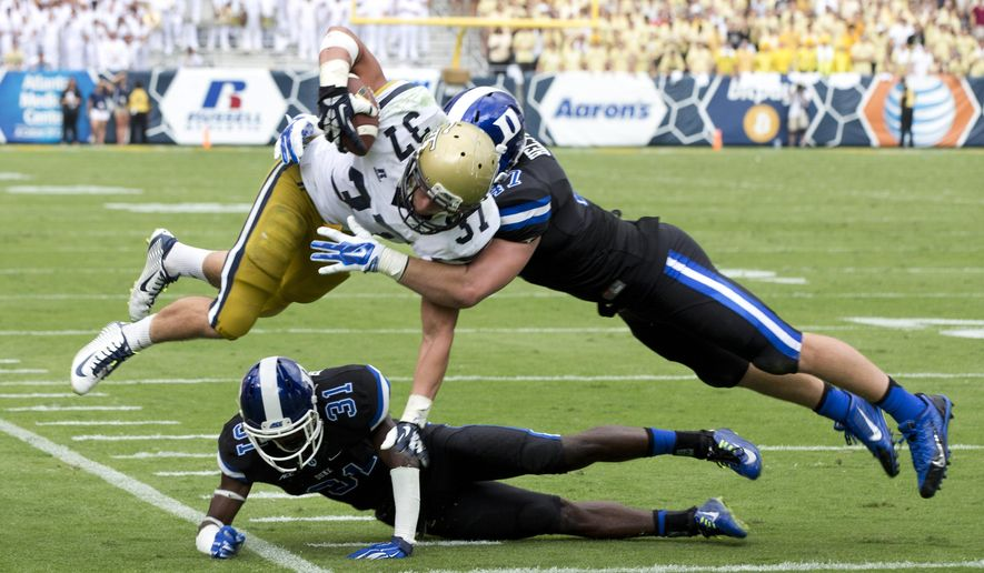 Georgia Tech running back Zach Laskey (37) is stopped short of the goal line by Duke defenders Breon Borders (31) and David Helton (47) after a catch in the first half of an NCAA college football game Saturday, Oct. 11, 2014, in Atlanta.  (AP Photo/John Bazemore)