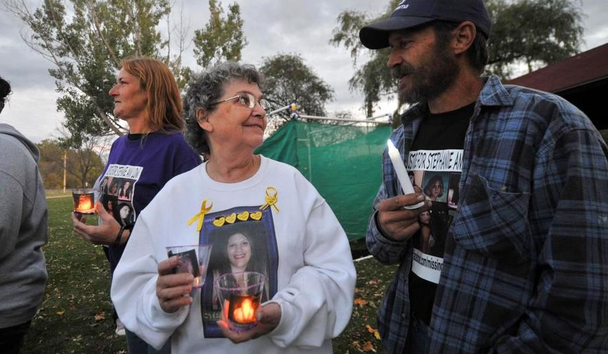 In this Oct. 10, 2014 photo, George Low, right,  father of Stephanie Low, and her grandmother Christie Low hold a candlelight vigil in memory of Stephanie Low at Oak Island Park in Wausau, Wis. Stephanie Low had been missing since October 2010. A Wisconsin prison inmate was charged last month with killing Low and burying her in the woods nearly four years ago after a botched robbery. (AP Photo/Wausau Daily Herald, T'xer Zhon Kha)