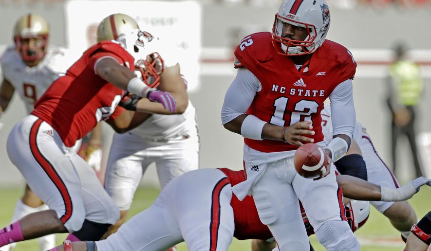 North Carolina State quarterback Jacoby Brissett (12) looks to hand off the ball during the first half of an NCAA college football game against Boston College in Raleigh, N.C., Saturday, Oct. 11, 2014. (AP Photo/Gerry Broome)