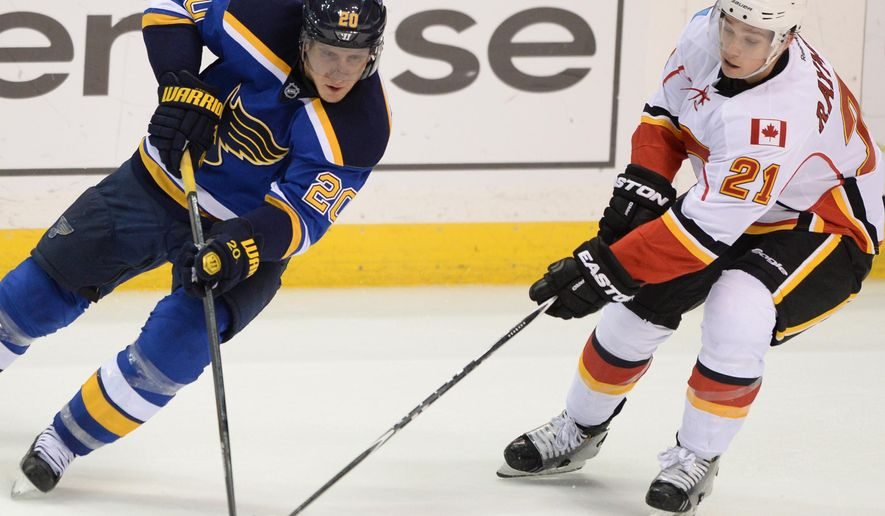 St. Louis Blues' Alexander Steen (20) and Calgary Flames' Mason Raymond (21) reach for the puck during the second period of an NHL hockey game, Saturday, Oct. 11, 2014, in St. Louis. (AP Photo/Bill Boyce)