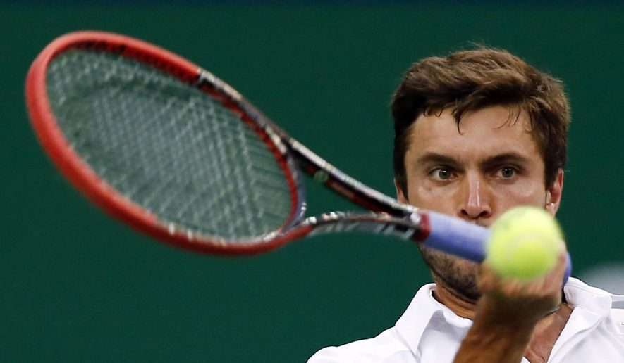 Gilles Simon of France returns a shot against Feliciano Lopez of Spain during their semifinal match at the Shanghai Masters tennis tournament in Shanghai, China, Saturday, Oct. 11, 2014.  (AP Photo/Vincent Thian)