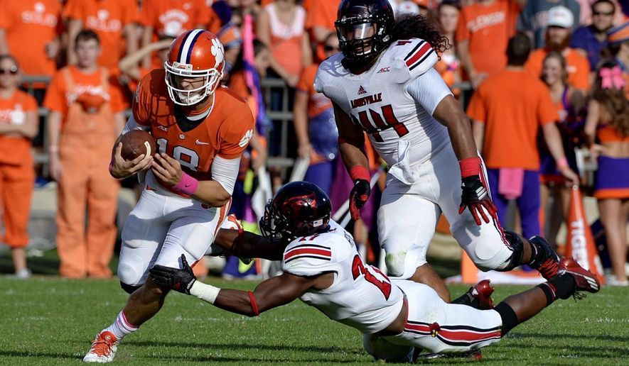 Clemson quarterback Cole Stoudt slips the tackle attempt of Louisville's Jermaine Reve during an NCAA college football game in Clemson, S.C., Saturday, Oct. 11, 2014. (AP Photo/ Richard Shiro)