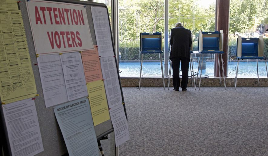 A lone voter takes part in early voting in Milwaukee in this Sept. 9, 2010, file photo. (AP Photo/Morry Gash)