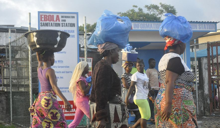 Liberia women walk past a sign warning people of the deadly Ebola virus in Monrovia, Liberia. Friday, Oct. 10, 2014. The number of people killed in the Ebola outbreak has risen above 4,000, according to the World Health Organization.  (AP Photo/ Abbas Dulleh)