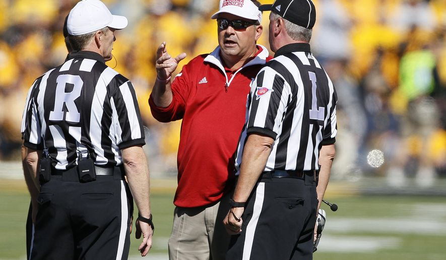 Indiana head coach Kevin Wilson, center, talks with officials after Indiana receives a sideline penalty during the first half of an NCAA college football game against Iowa, Saturday, Oct. 11, 2014, in Iowa City, Iowa. (AP Photo/Matthew Putney)