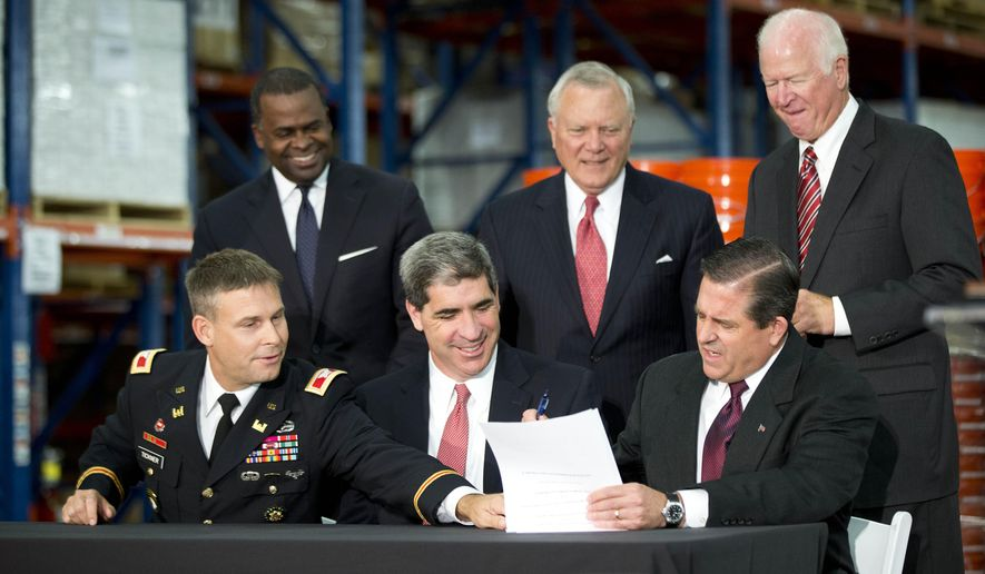 Georgia Department of Transportation commissioner Keith Golden, center, Georgia Port Authority executive director Curtis Foltz, right, and Col. Thomas Tickner, with U.S. Army Corp of Engineers sign a cost-sharing agreement for the Savannah Harbor Expansionas as Atlanta Mayor Kasim Reed, left rear, Gov. Nathan Deal, center rear, and  and Sen. Saxby Chambliss, R-Ga., look on  Project  at the Home Depot Direct Fulillment Center  Wednesday, Oct. 8, 2014, in Locust Grove , Ga. The expansion will allow larger ships to use the port.  (AP Photo/John Bazemore)