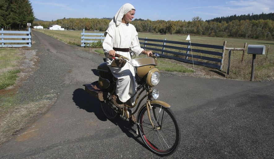 In this photo on Wednesday, Oct. 8, 2014, Cheryl Cutler rides a bike that she built herself from old bike parts, recycled mobile home siding and kitchen pots near Lorane, Ore. Cheryl and her husband Eli Cutler have chosen to live a simple life as they caretake property in rural Lane County south of Eugene. (AP Photo/The Register-Guard, Collin Andrew)
