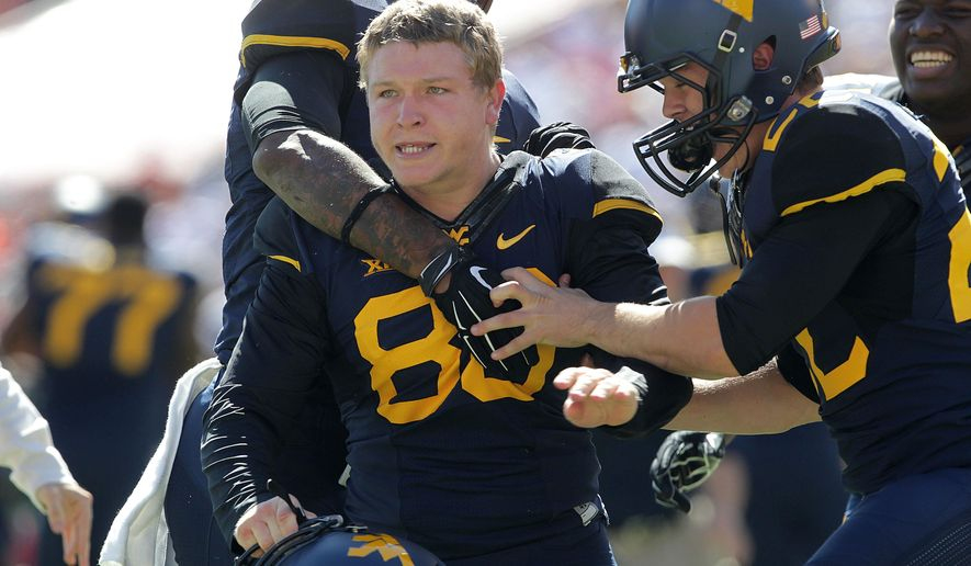 West Virginia's Josh Lambert (86) is greeted by teammates after hitting a game winning 55-yard field goal against Texas Tech during a NCAA college football game in Lubbock, Texas, Saturday, Oct. 11, 2014. (AP Photo/Lubbock Avalanche-Journal, Tori Eichberger)
