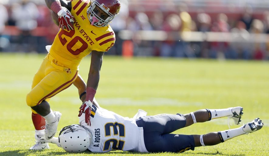 Iowa State running back DeVondrick Nealy breaks away from a tackle by Toledo defensive back DeJuan Rogers (23) during the first half of an NCAA football game, Saturday, Oct. 11, 2014, in Ames, Iowa. (AP Photo/Justin Hayworth)