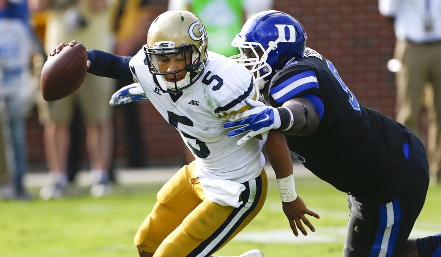 Georgia Tech quarterback Justin Thomas (5) is pressured by Duke defensive tackle Carlos Wray (98) in the second half of an NCAA college football game Saturday, Oct. 11, 2014, in Atlanta.  Duke won 31-25. (AP Photo/John Bazemore)