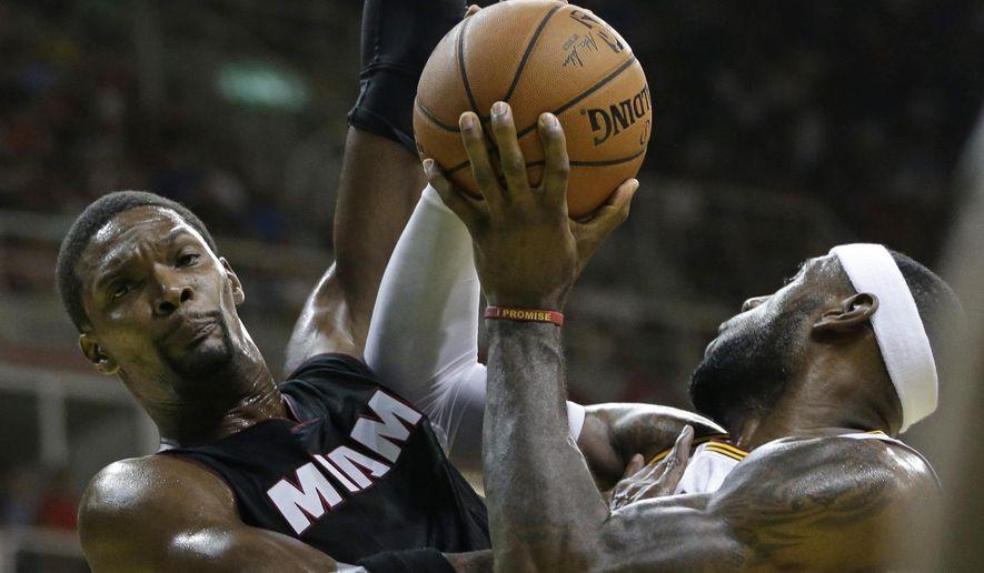 Cleveland Cavaliers' LeBron James, right, tries to shoots past Miami Heat's Chris Bosh during a NBA preseason basketball game that's part of the NBA Global Games, in Rio de Janeiro, Brazil, Saturday, Oct. 11, 2014. (AP Photo/Felipe Dana)