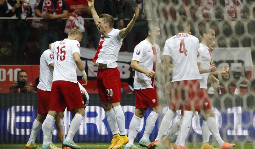 Poland's Arkadiusz Milik, right, celebrates with this teammates after scoring the opening goal during a Euro 2016 group D qualifying soccer match between Poland and Germany in Warsaw, Poland,Saturday, Oct. 11, 2014. (AP Photo/Czarek Sokolowski)