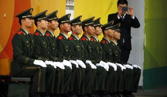 A man takes pictures next to Chinese paramilitary policemen sitting on a bench before a friendly soccer match between Argentina and Brazil at the Bird's Nest National Stadium in Beijing, China, Saturday, Oct. 11, 2014. (AP Photo/Ng Han Guan) ** FILE **