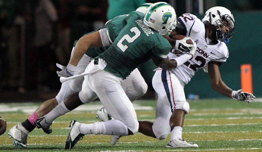 Tulane safety Darion Monroe (2) creates a fumble by stripping the ball away from Connecticut running back Arkeel Newsome (22) during an NCAA college football game in New Orleans, Saturday, Oct. 11, 2014. (AP Photo/The New Orleans Advocate, A.J. Sisco) NO SALES; MAGAZINES OUT; INTERNET OUT; TV OUT; NO FOREIGNS. LOUISIANA BUSINESS INC. OUT (INCLUDING GREATER BATON ROUGE BUSINESS REPORT; 225; 10/12; INREGISTER; LBI CUSTOM); MANDATORY CREDIT