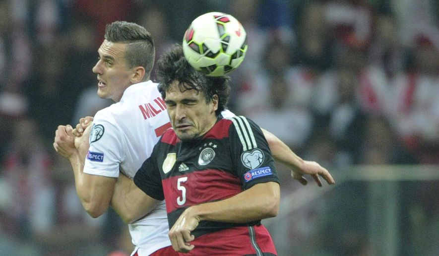 Poland's Arkadiusz Milik, left, and Germany's Mats Hummels go for a header during a Euro 2016 group D qualifying soccer match between Poland and Germany in Warsaw, Poland, Saturday, Oct. 11, 2014. (AP Photo/Alik Keplicz)
