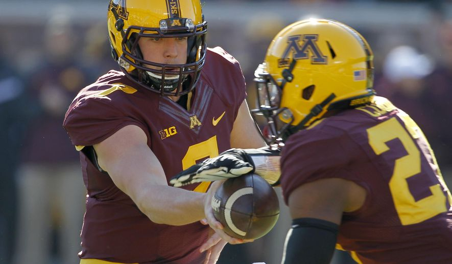 Minnesota quarterback Mitch Leidner, left, hands off the ball to running back David Cobb during the first quarter of an NCAA college football game against Northwestern in Minneapolis, Saturday, Oct. 11, 2014. (AP Photo/Ann Heisenfelt)