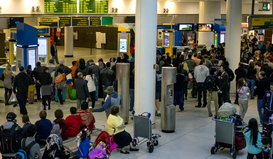 Passengers stand, most waiting for incoming flights, in the arrivals area at John F. Kennedy International Airport (JFK) in New York, Saturday, Oct. 11, 2014. Health screening procedures were put in place at the airport today to check the health of people arriving from Ebola-affected countries. (AP Photo/Craig Ruttle)