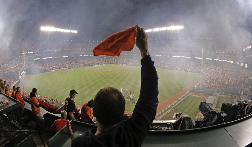 Fans cheers from the center field seats before of Game 1 of the American League baseball championship series between the Baltimore Orioles and the Kansas City Royals Friday, Oct. 10, 2014, in Baltimore. (AP Photo/Charlie Riedel)