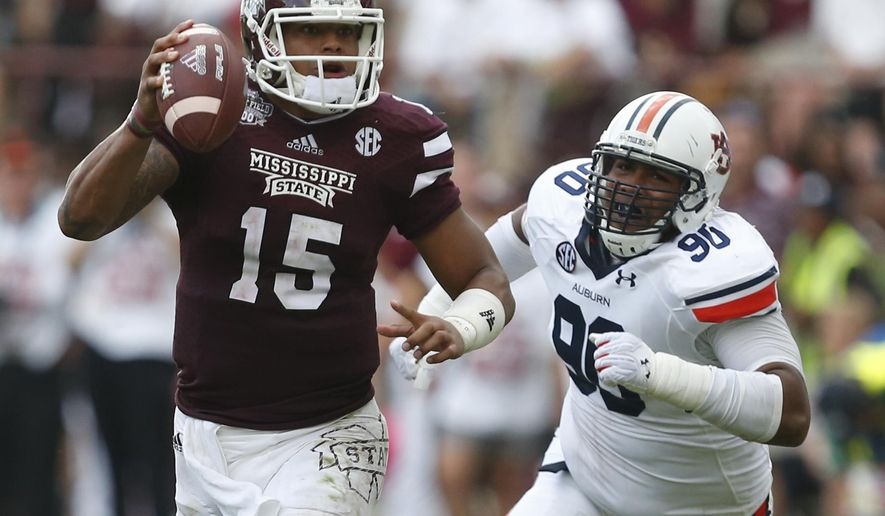 Mississippi State quarterback Dak Prescott (15) is pursued by Auburn defensive lineman Gabe Wright (90) during the first half of an NCAA college football game in Starkville, Miss., Saturday, Oct 11, 2014.  (AP Photo/Rogelio V. Solis)