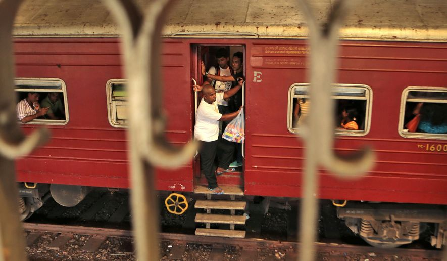 """People ride a train that is about to reach Fort railway station in Colombo, Sri Lanka, Saturday, Oct. 11, 2014. The """"Queen of Jaffna,"""" a once-popular train linking the ethnic Tamil's northern heartland to the rest of Sri Lanka before a bloody civil war cut the link 24 years ago, chugs back into service next week, reinforcing the government's authority in a region once controlled by Tamil rebels. President Mahinda Rajapaksa will inaugurate service along the 400-kilometer (250-mile) route between Jaffna and Colombo, the capital, in a ceremony Monday. (AP Photo/Eranga Jayawardena)"""