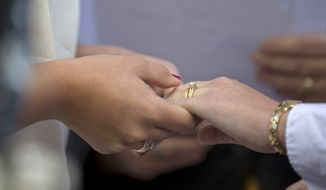 Jennifer Melsop, left, 26, and Erika Turner, 26, from Centreville, Va., hold hands after exchanging wedding rings during a ceremony officiated by the Rev. Linda Olson Peebles in front of the Arlington County Courthouse in Arlington, Va., Monday, Oct. 6, 2014. (AP Photo/Manuel Balce Ceneta) **FILE**