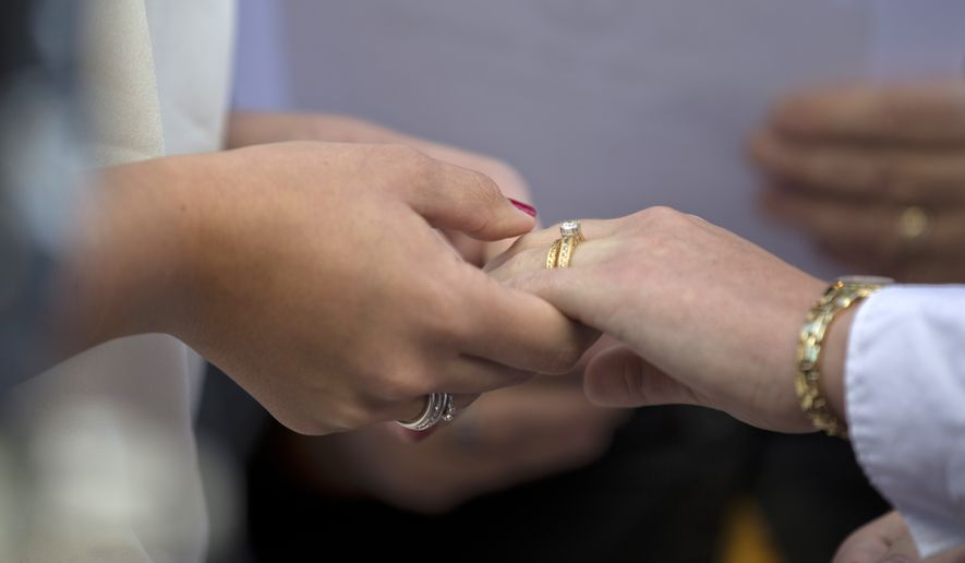 In this file photo, two women from Centreville, Va., hold hands after exchanging wedding rings during a ceremony in front of the Arlington County Courthouse in Arlington, Va., Monday, Oct. 6, 2014. A Virginia photographer, Chris Herring, is suing the state over a new law taking effect in July 2020. Mr. Herring says the law will infringe on his First Amendment rights by requiring him to promote same-sex weddings on his website. Mr. Herring has religious scruples that forbid him to photograph such ceremonies and argues in a court filing his free-speech rights are also infringed by the legislation. (AP Photo/Manuel Balce Ceneta) **FILE**