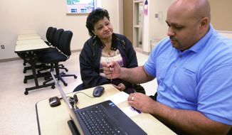 Else Trinidad gets help  from Omar Bonet of SRA international about information regarding ACA health insurance options in Paterson, NJ, Friday, Oct. 10, 2014. (AP Photo/The Record of Bergen County, Viorel Florescu) (AP Photo/The Record, VIOREL FLORESCU)