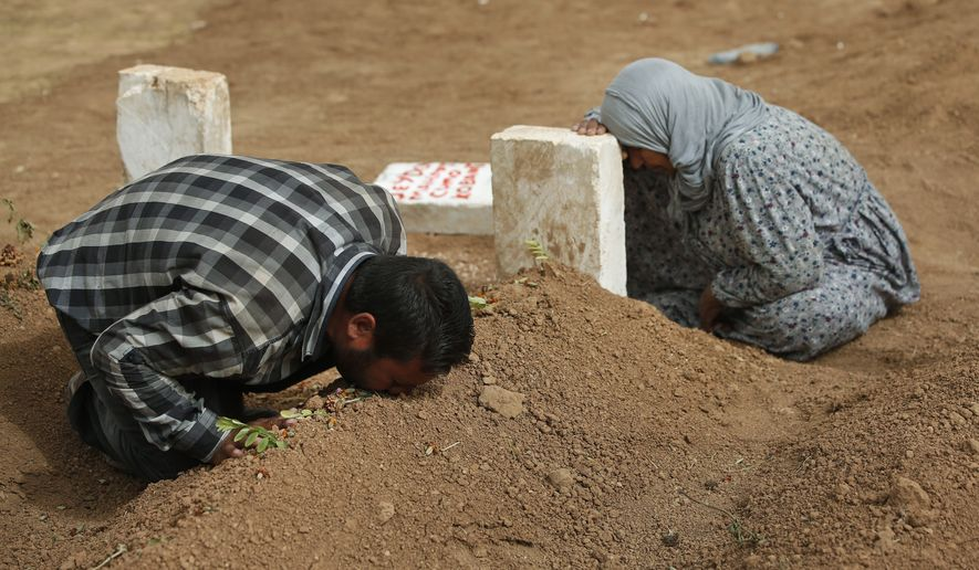 Kurdish Rabia Ali, right, accompanied by her son Ali Mehmud, left, mourn on Saturday, Oct. 11, 2014, at the grave of her son Seydo Mehmud 'Curo' , a Kurdish fighter, who was killed in the fighting with the militants of the Islamic State group in Kobani, Syria, and was buried at a cemetery in Suruc, on the Turkey-Syria border on Tuesday, Oct. 7. Kobani, also known as Ayn Arab, and its surrounding areas, has been under assault by extremists of the Islamic State group since mid-September and is being defended by Kurdish  fighters. (AP Photo/Lefteris Pitarakis)