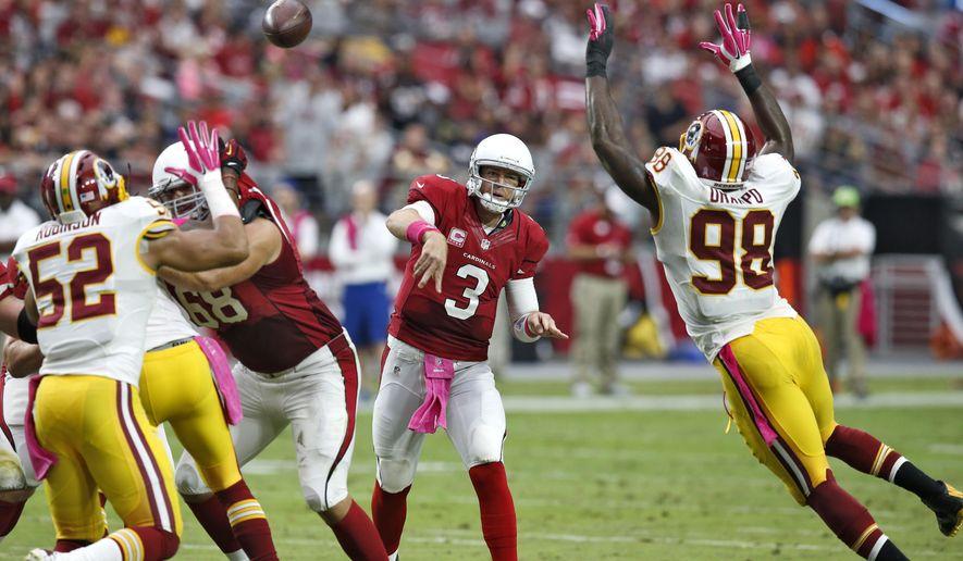 Arizona Cardinals quarterback Carson Palmer (3) throws as Washington Redskins outside linebacker Brian Orakpo (98) pursues during the first half of an NFL football game, Sunday, Oct. 12, 2014, in Glendale, Ariz. (AP Photo/Rick Scuteri)