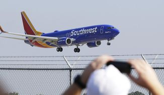 FILE - In this Sept. 8, 2014 file photo, a Southwest Airlines plane with a new paint job flies over Love Field in Dallas. On Monday, Oct. 13, 2014, Southwest will launch its first long-distance flights from its home base at Dallas Love Field to seven cities across the country, with eight more destinations next month. Such flights were prohibited until now by a longtime law that protected Dallas-Fort Worth International Airport by limiting flights from Love Field to a few nearby states. (AP Photo/LM Otero, File)