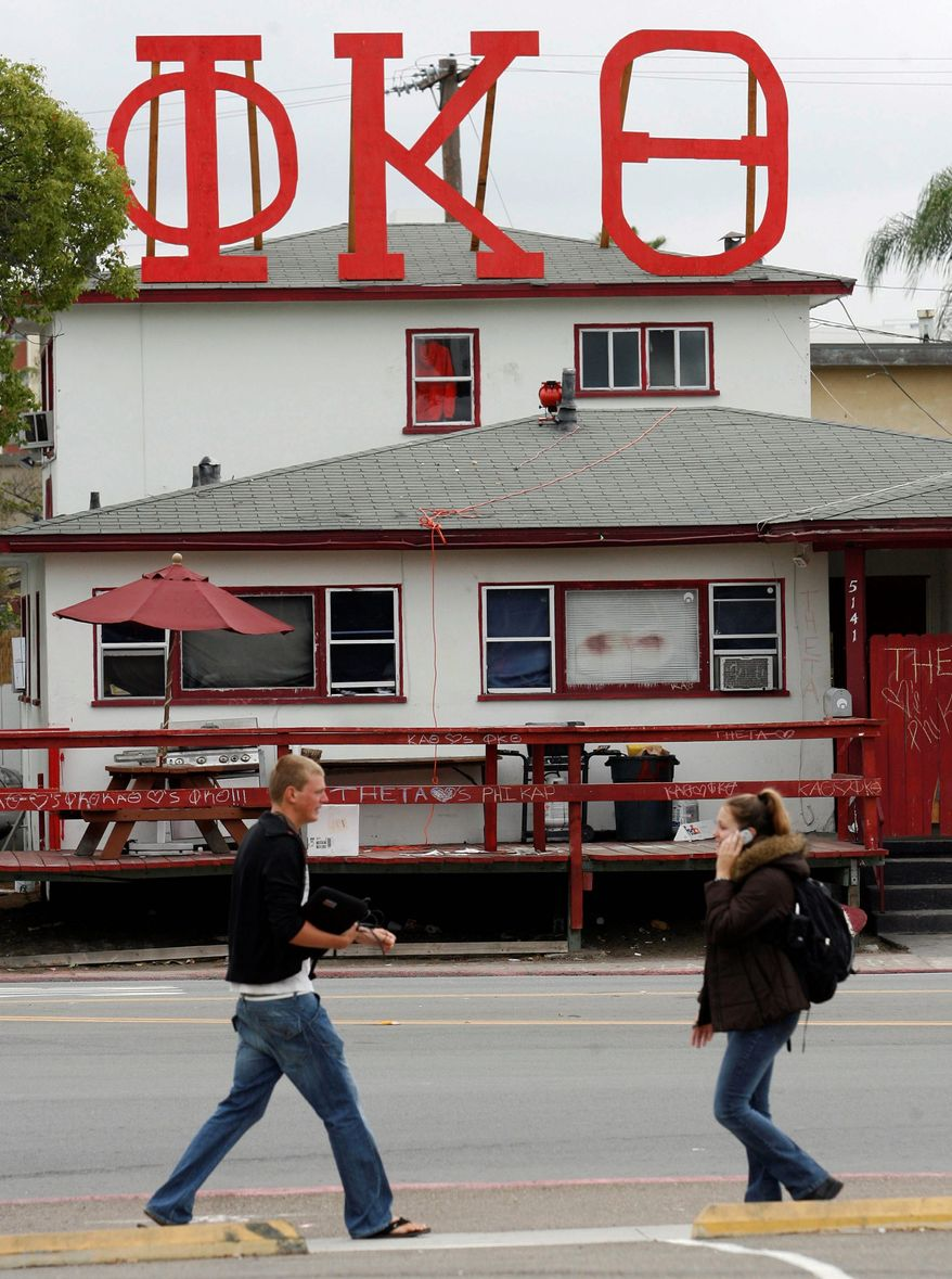 Students walk past the Phi Kappa Theta fraternity house at San Diego State University in San Diego. San Diego State University says it has suspended the fraternity until it completes an investigation of a student who was found dead at its house after a party.(AP Photo/Denis Poroy,File)