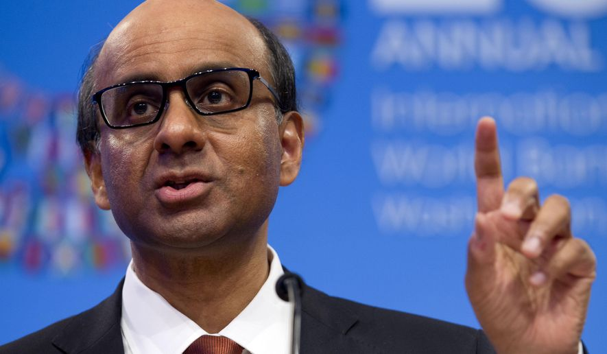 IMFC Chair and Singapore's Finance Minister Tharman Shanmugaratnam accompanied by International Monetary Fund (IMF) Managing Director Christine Lagarde speaks during a news conference at the World Bank Group-International Monetary Fund Annual Meetings at IMF headquarters in Washington, Saturday, Oct. 11, 2014.  (AP Photo/Jose Luis Magana)