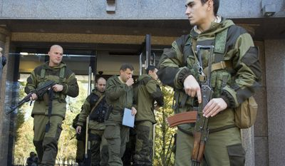 Alexander Zakharchenko, Prime Minister of the self proclaimed 'Donetsk People's Republic', centre,  surrounded by pro-Russian rebels, walks in the town of Donetsk, eastern Ukraine Saturday, Oct. 11, 2014. (Associated Press) ** FILE **
