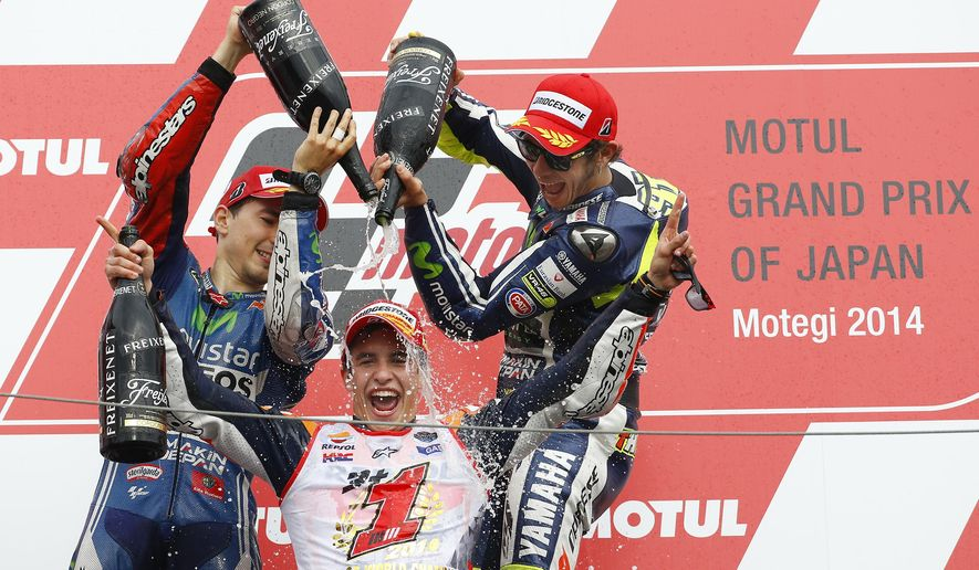 Spain's Marc Marquez is sprayed champagne by race winner and compatriot Jorge Lorenzo, left, and third-placed Valentino Rossi of Italy, right, during the awarding ceremony of Japanese Motorcycle Grand Prix at Twin Ring Motegi circuit in Motegi, north of Tokyo, Japan, Sunday, Oct. 12, 2014. Honda rider Marquez defended his MotoGP championship on Sunday when he finished second in the Grand Prix of Japan behind compatriot Lorenzo. (AP Photo/Shizuo Kambayashi)