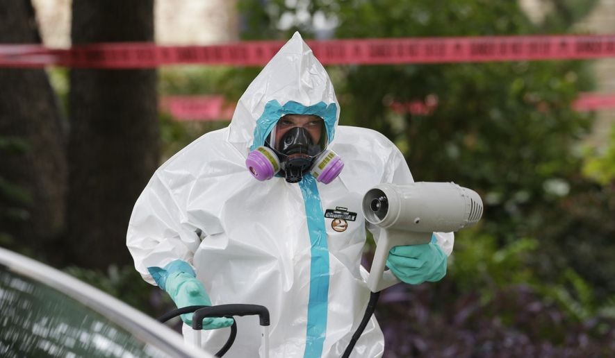 A hazmat worker cleans outside the apartment building of a hospital worker, Sunday, Oct. 12, 2014, in Dallas. The Texas health care worker, who was in full protective gear when they provided hospital care for Ebola patient Thomas Eric Duncan, who later died, has tested positive for the virus and is in stable condition, health officials said Sunday. (AP Photo/LM Otero)