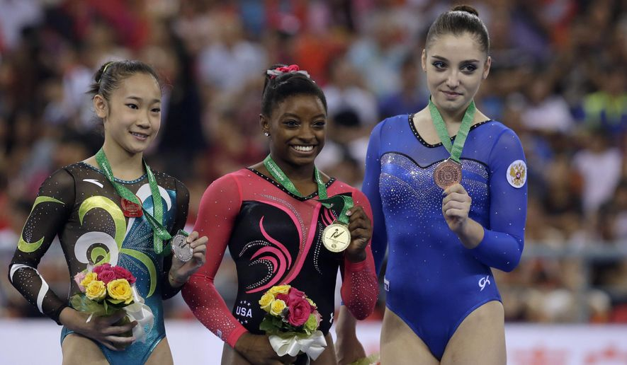 Gold Medalist Simone Biles of the U.S., center, second placed Bai Yawen of China, left, and Aliya Mustafina of Russia pose on podium at the awards ceremony of the women's balance beam final of the Artistic Gymnastics World Championship at the Guangxi Gymnasium in Nanning, capital of southwest China's Guangxi Zhuang Autonomous Region Sunday, Oct. 12, 2014. (AP Photo/Andy Wong)