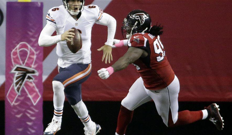Chicago Bears quarterback Jay Cutler (6) runs from Atlanta Falcons defensive end Jonathan Babineaux (95) during the second half of an NFL football game, Sunday, Oct. 12, 2014, in Atlanta. (AP Photo/David Goldman)