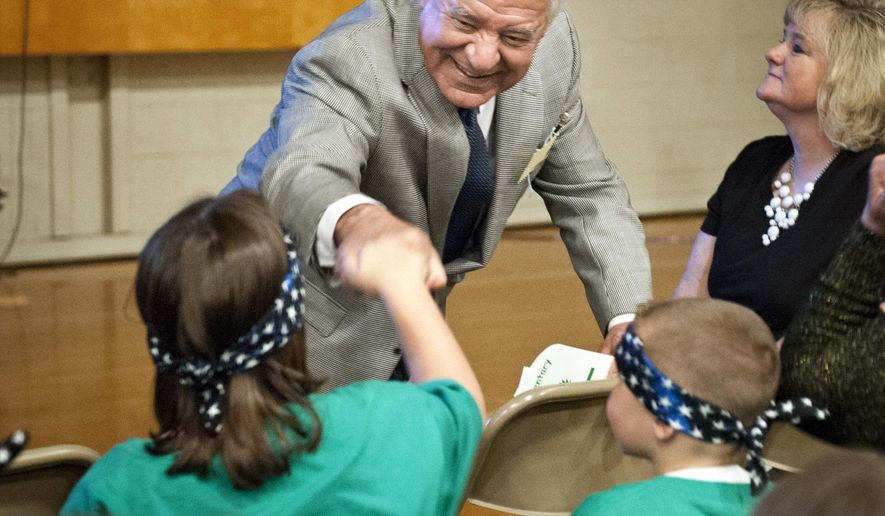 """FILE - U.S. Rep. Nick Rahall greets Oakvale Elementary School students with a fist bump prior to the school's dedication ceremony in Princeton, W.Va., Monday, April 21, 2014. Rahall, known around his southern district as """"Nick Joe,"""" is facing the toughest fight for his job in four decades. (AP Photo/Michael Shroyer, File)"""