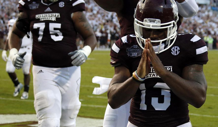 Mississippi State running back Josh Robinson (13) celebrates his 1-yard second-half touchdown run against Auburn as teammates run over to congratulate him in an NCAA college football game in Starkville, Miss., Saturday, Oct 11, 2014. Mississippi State won 38-23. (AP Photo/Rogelio V. Solis)