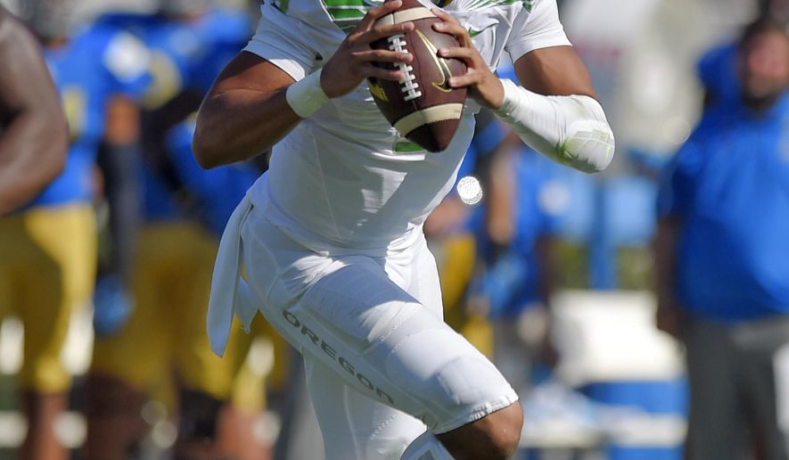 Oregon quarterback Marcus Mariota gets set to pass during the second half of a NCAA college football game against Oregon, Saturday, Oct. 11, 2014, in Pasadena, Calif. Oregon won 42-30. (AP Photo/Mark J. Terrill)