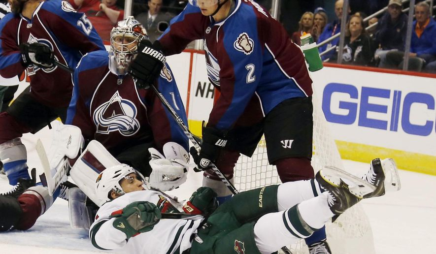 Minnesota Wild left wing Zach Parise, front, falls to the ice after being hit by Colorado Avalanche defensman Nick Holden while redirecting a shot on Avalanche goalie Semyon Varlamov, back, of Russia, during a Wild power play late in the first period of a hockey game in Denver on Saturday, Oct. 11, 2014. (AP Photo/David Zalubowski)